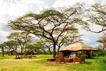 Couple relaxing in their mobile tented camp in the Serengeti, Tanzania