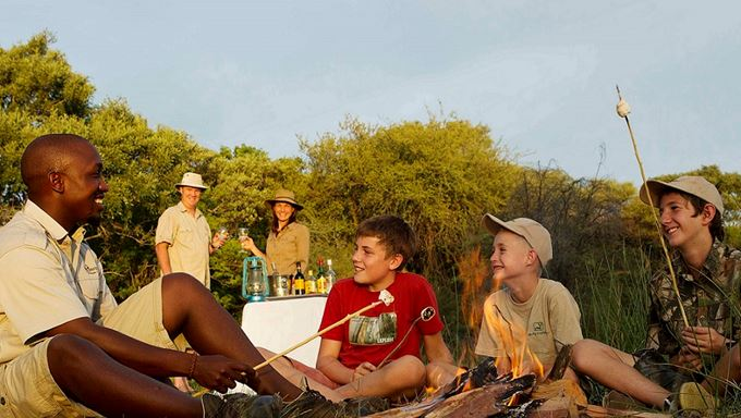 Guide and family toasting marshmallows on a campfire in Botswana