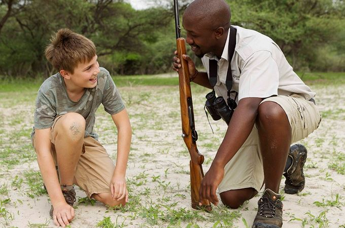 Botswana family safari guide with boy looking at tracks
