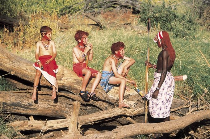 Children learning from Maasai guide on family safari in Kenya
