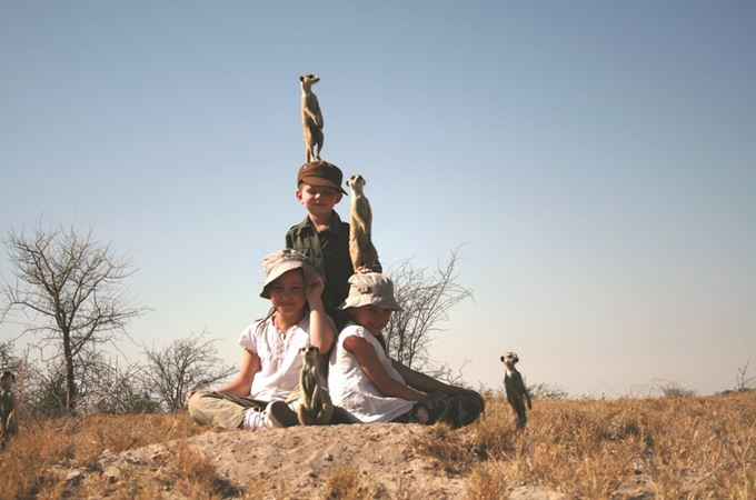 Meerkats standing on children's heads on Botswana family safari in the desert