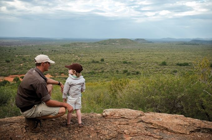 Child and safari guide looking over South Africa on malaria free family holiday