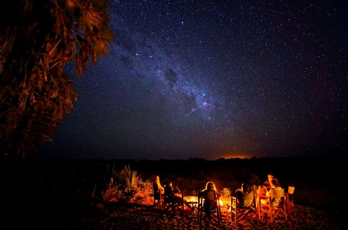 Sitting around the campfire under the stars on a fly camping walking safari in Ruaha Tanzania